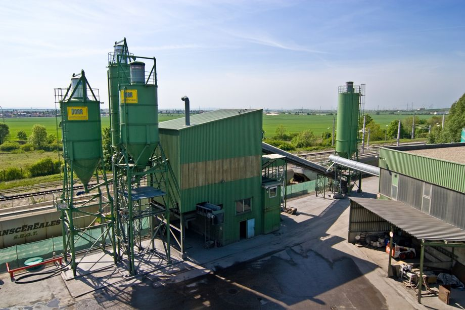 Photo: Stabilising system: industrial plant painted in green with silos and two buildings connected to one another through conveyor belts.