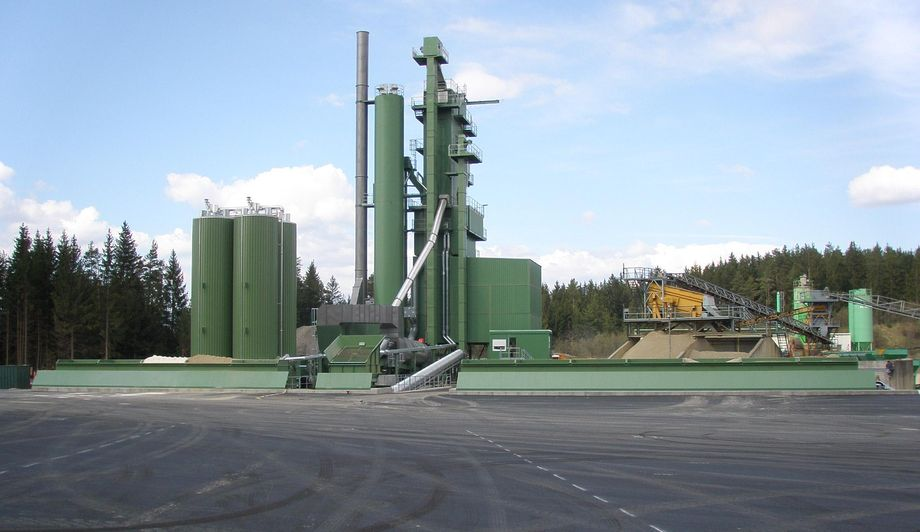 Photo: Lieferasphaltgesellschaft Jauntal asphalt mixing plant: asphalt mixing plant coated in light green standing on a spacious asphalted site; forests in the background