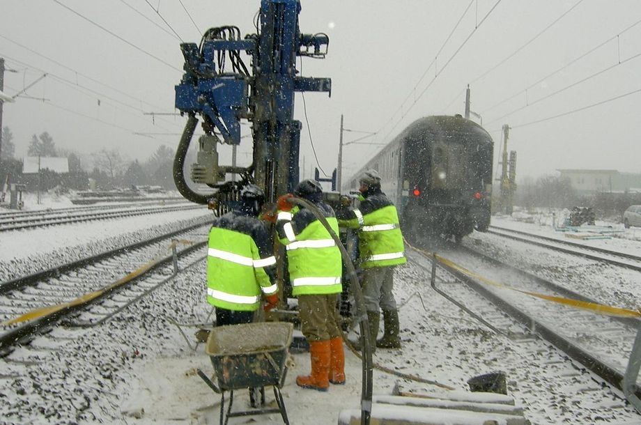 Photo: Himberg: Three workers in neon yellow vests drilling between snow-covered rail tracks