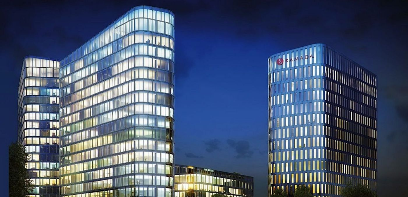 3D rendering: Bavaria Towers: Night view of the ensemble being created; two high-rise buildings with glass façades and rounded off corners from a worm's-eye view.
