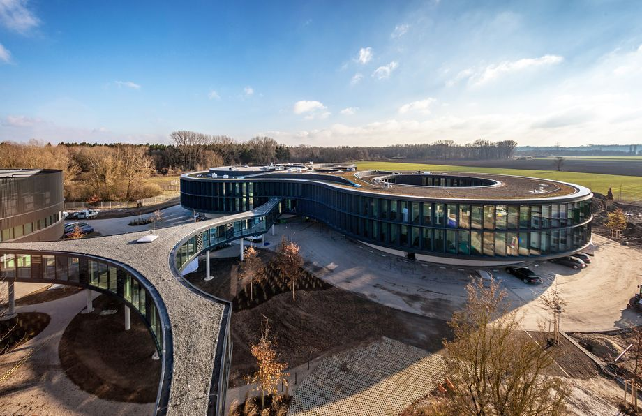 Photo: ESO Garching – The oval building with a large opening in the flat roof and the one-story linking block to the other parts of the building, standing on stilts