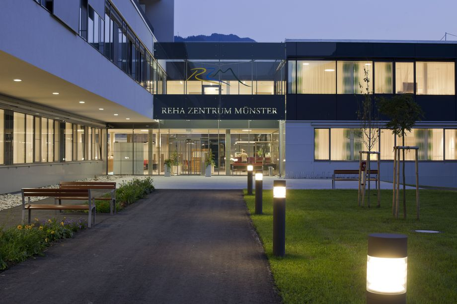 Photo: Münster rehabilitation centre An illuminated path leads to the building entrance with glass front