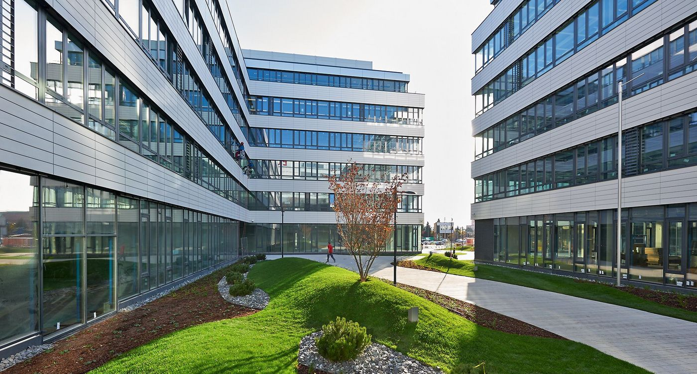 Photo: EURO PLAZA 5: area between three buildings with glass façades. A paved path leads through a lovingly landscaped green area.