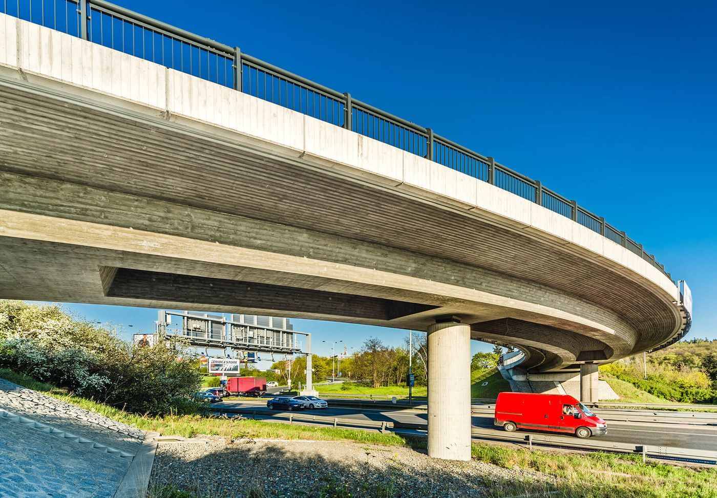 Photo: concrete bridge from below; underneath, a multi-lane motorway with vehicle traffic