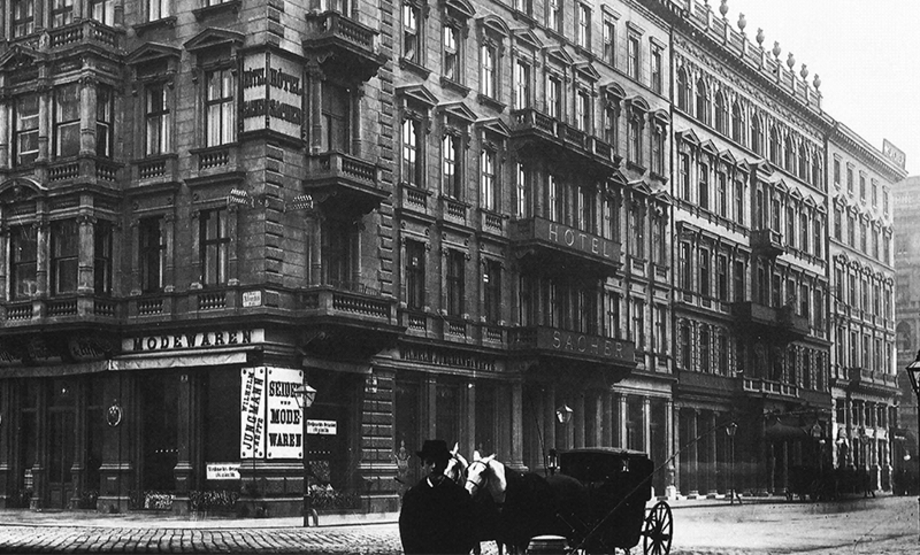 "Black and white photo: view of a corner of a building, rows of windows and balconies, a sign that is barely legible as reading ""Hotel Sacher"" at the corner, above a sign for a shop selling fashion goods. To the right, lettering on the building balconies reads ""Hotel Sacher"", in front stands a carriage with two horses, a man in a black coat and a hat, his face barely visible, and further building façades behind"