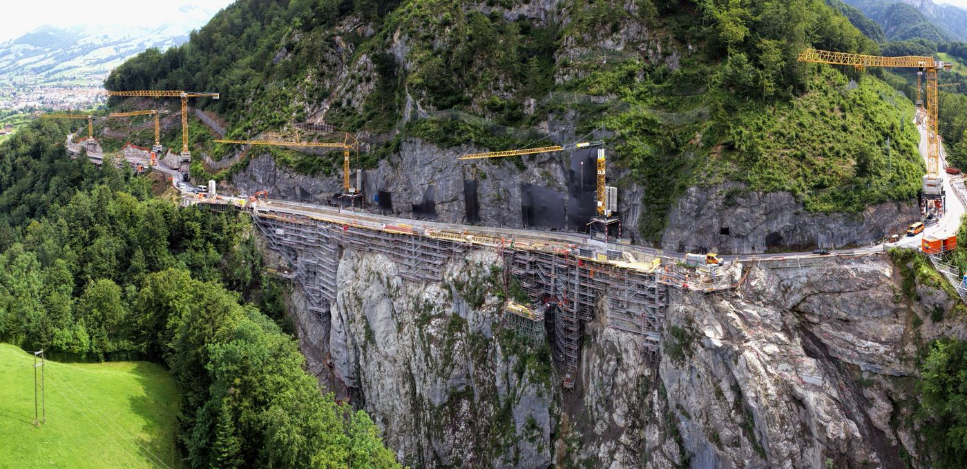 Photo: entirety of a mountain construction site; road running along a vertical cliff face; six cranes, scaffolding, grating and construction vehicles; to left, bright green fields and trees; to left behind, a mountain panorama