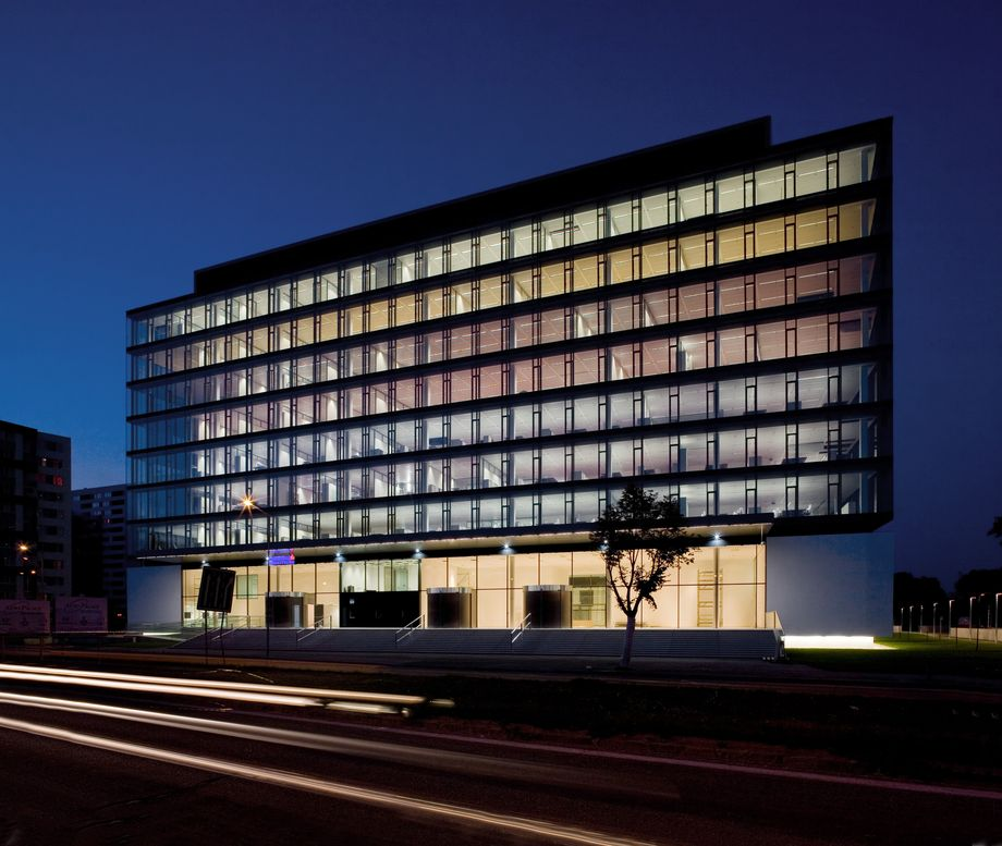 Photo: SLSP Headoffice, Bratislava – 12-storey, multicoloured illuminated bank building with transparent glass facade by night