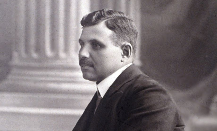 Black and white photo: man wearing a suit, photographed from the side, dark hair, side parting, moustache, not looking directly at the camera, the outline of a pillar can be seen in the background