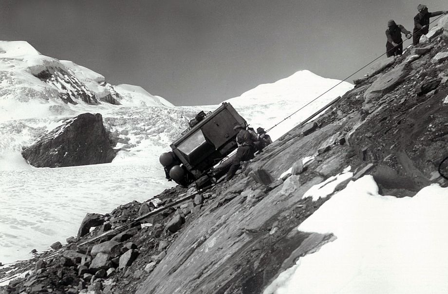 Black and white photo: construction workers using rope equipment for transport up the mountain over steep, rocky ground