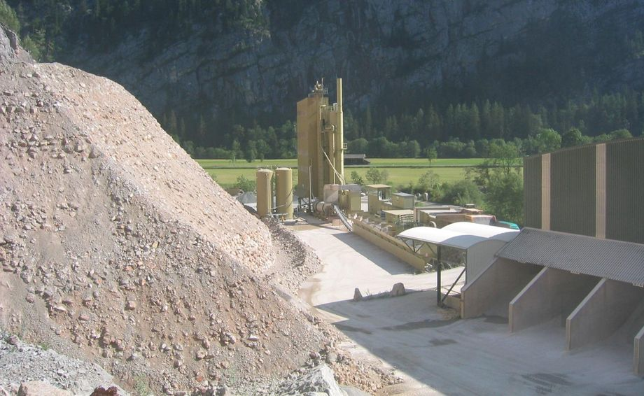 Photo: Weißbach asphalt mixing plant: asphalt mixing plant coated in beige in front of a partially forested rock face; sand mounds raised high in the foreground
