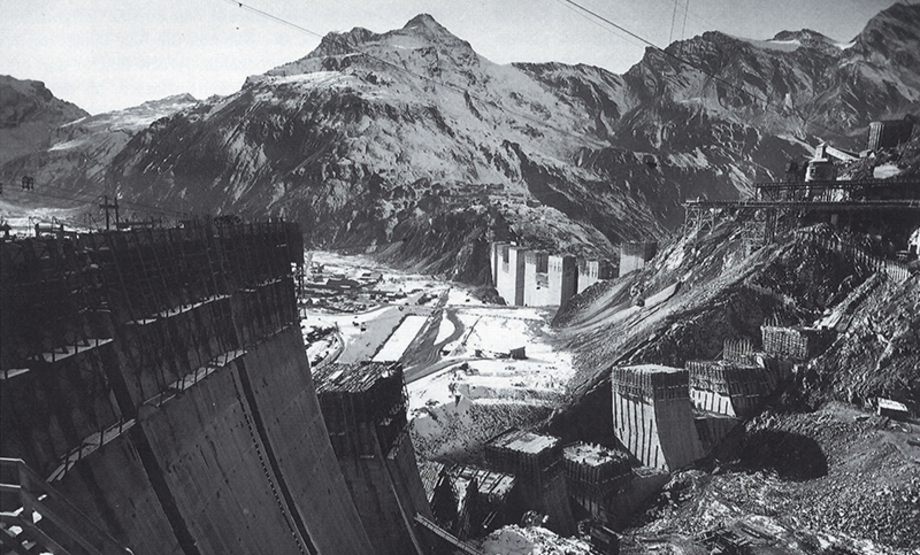 Black and white photo: power station under construction in a valley, stony surroundings, individual sections of the power station can be seen, not yet connected to one another, concrete dam with scaffolding on the left, more scaffolding on the right, construction elements and power lines, snow-covered mountains in the background
