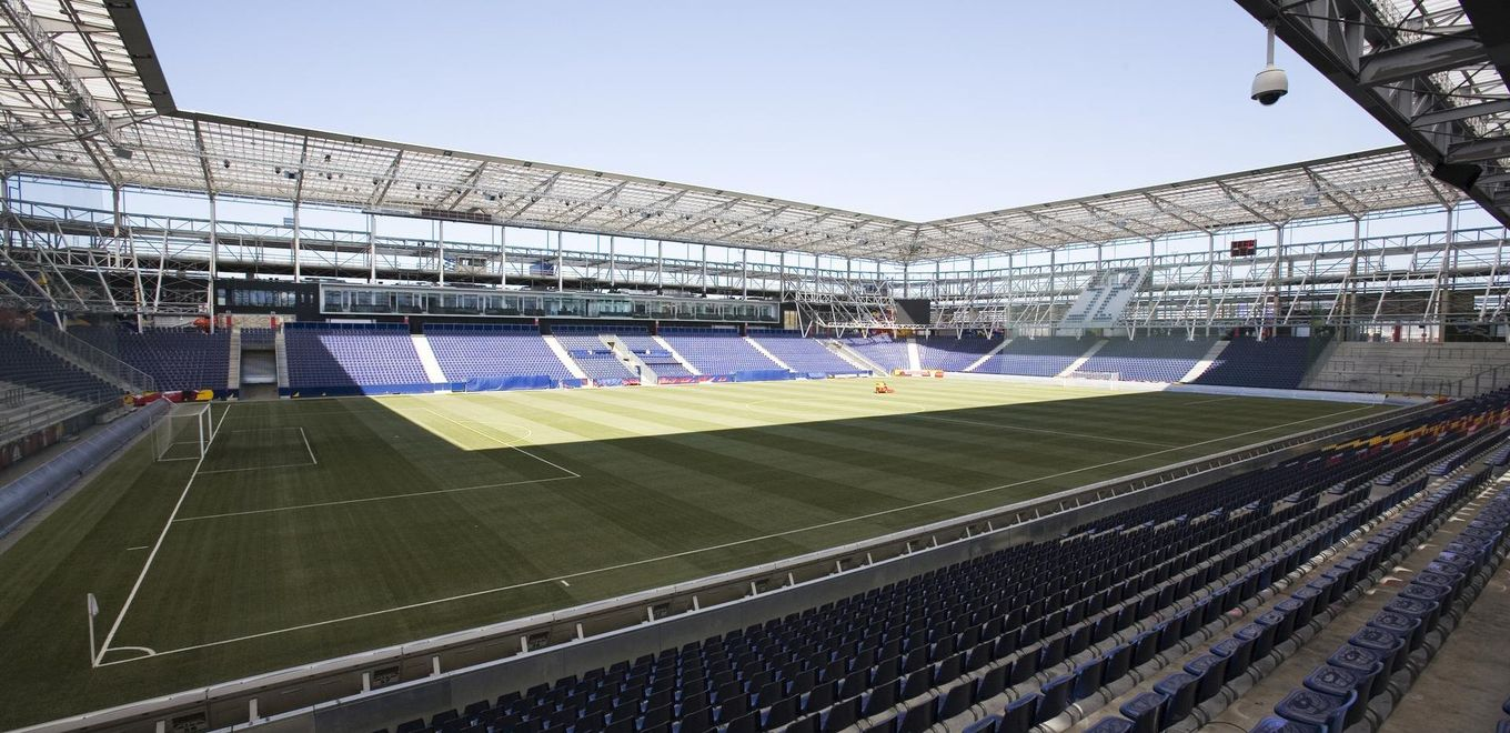 Photo: Red Bull Arena: Interior view of the football stadium under a blue sky from a corner