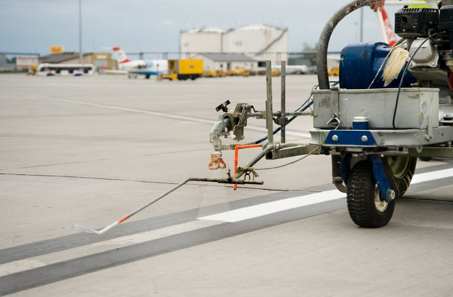 Photo: Road marking: A vehicle equipped with a spraying device applies white colour to a masked area of an airport runway.