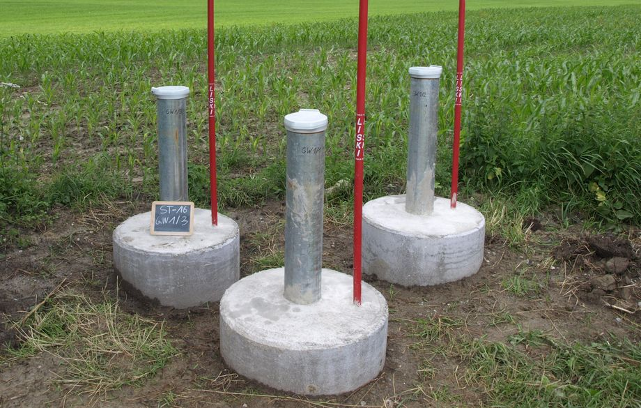 Photo: Three groundwater measurement points next to a field in a green mountainous landscape