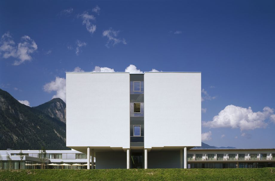 Photo: Münster rehabilitation centre View onto a three storey building with a white façade in front of an idyllic mountain landscape
