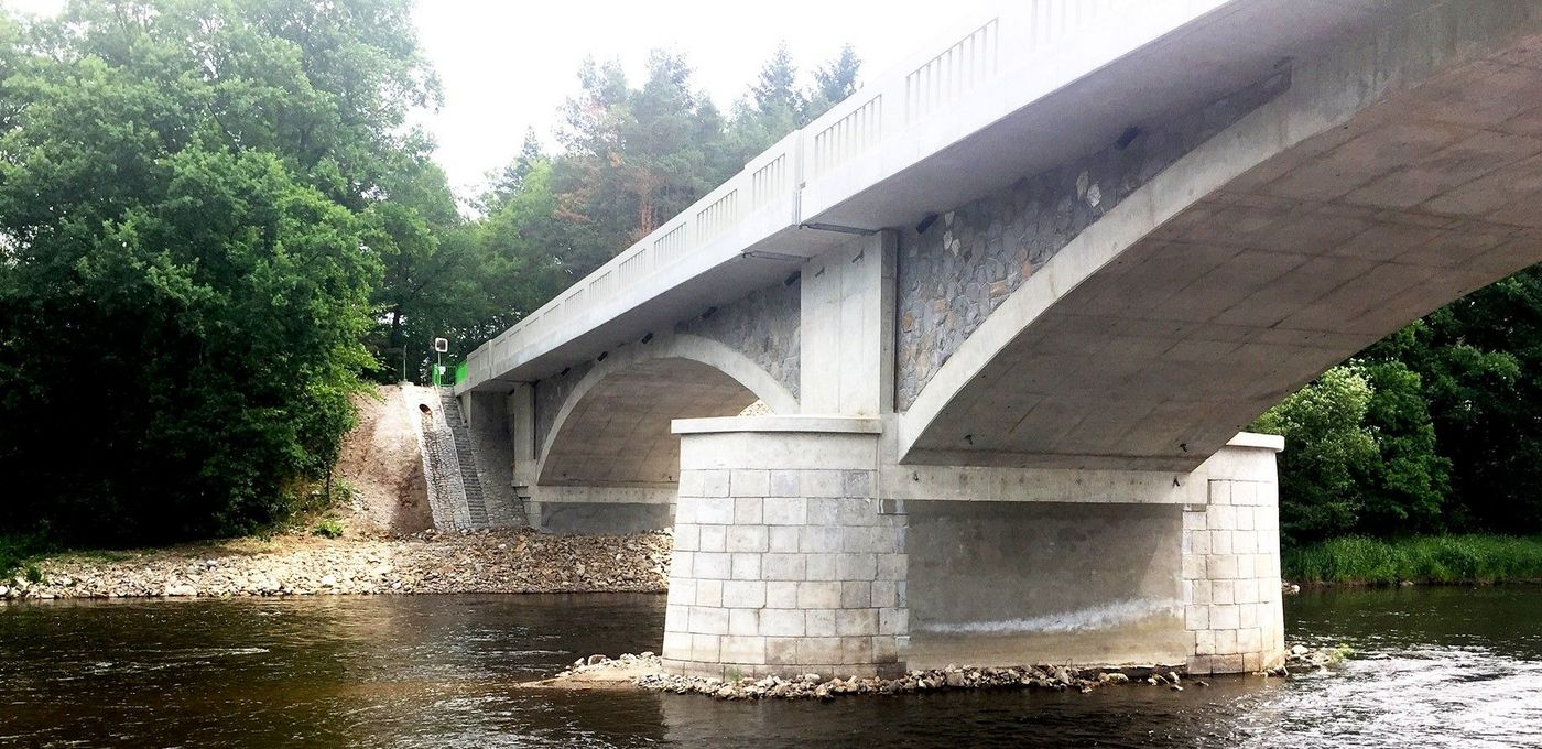 Photo: view from below of a new bridge structure in historic style; underneath, a narrow river with a wooded bank on the opposite side