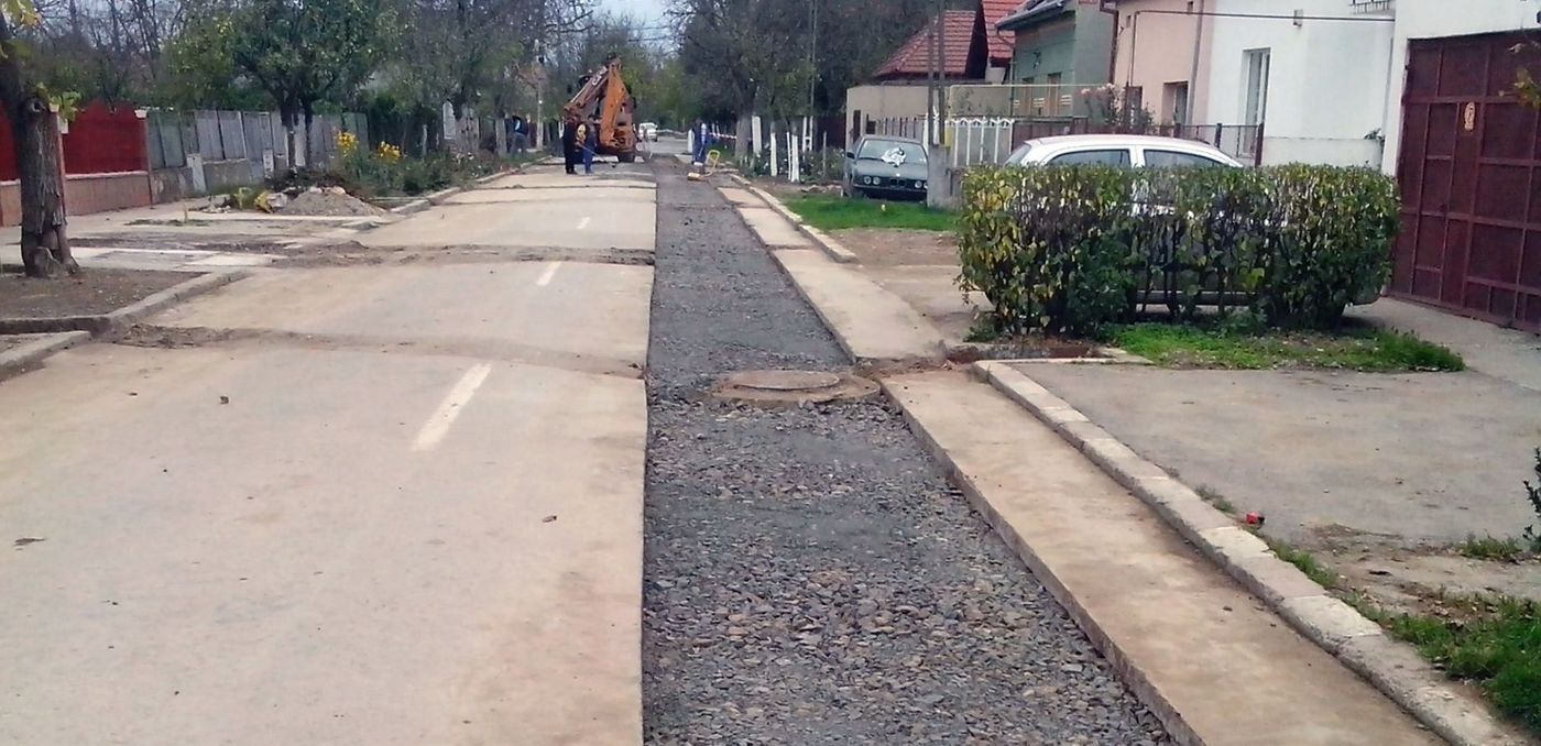 Photo: view of a street which has partly been opened and covered with porous asphalt; on the right, houses, driveways, cars, power lines; in the background, construction machines, trees, a mostly grey and cloudy sky