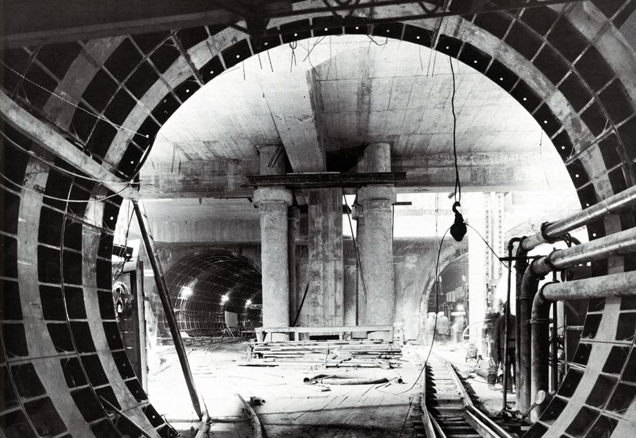 : Black and white photo: view from a tunnel being completed, rails leading into two other, illuminated tunnels, separated by supporting columns