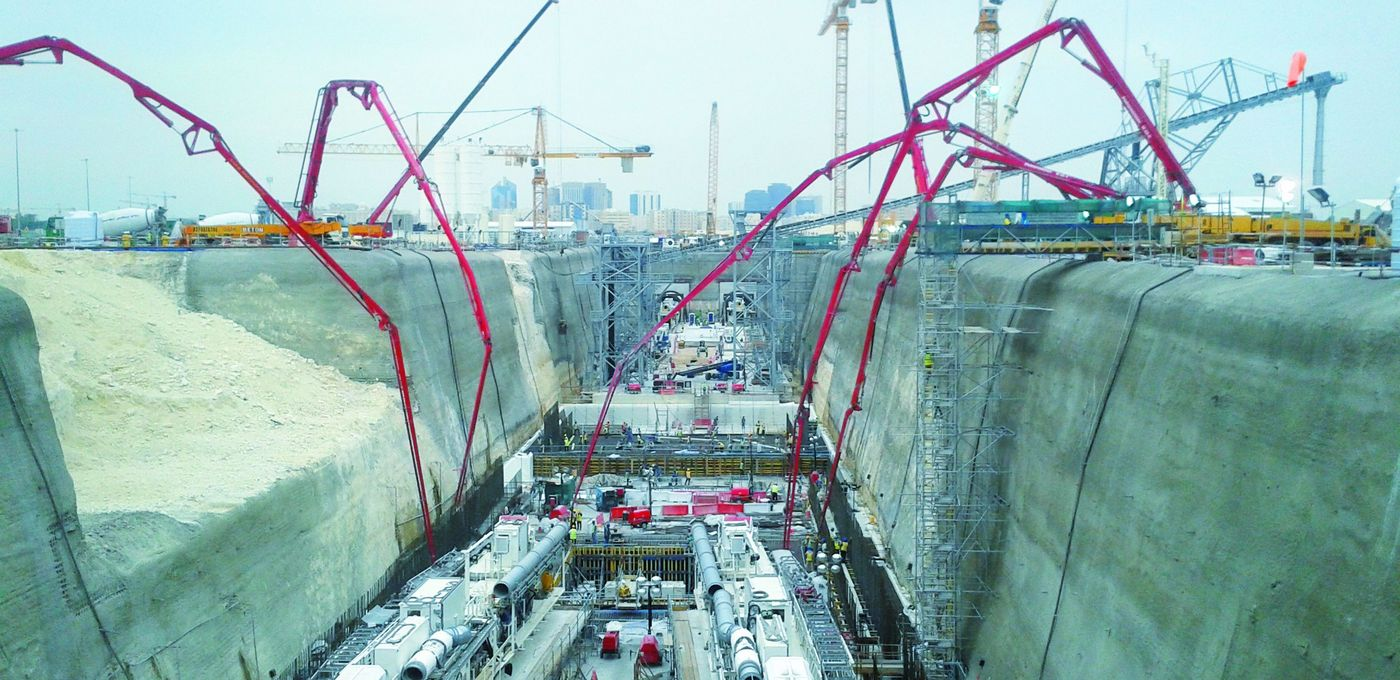 Photo: Green Line, Metro Doha: Longitudinal view of a deep construction pit with complex construction site equipment; several mobile concrete pumps stretching their long arms onto the pit's floor at the pit's edge