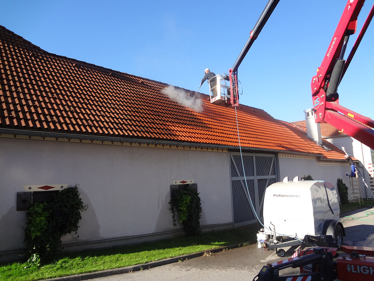 Photo: Roof coating: From a crane manbasket, a worker cleans the red brick roof with a high-pressure water jet device before the coating can be applied to the single-storey roof.