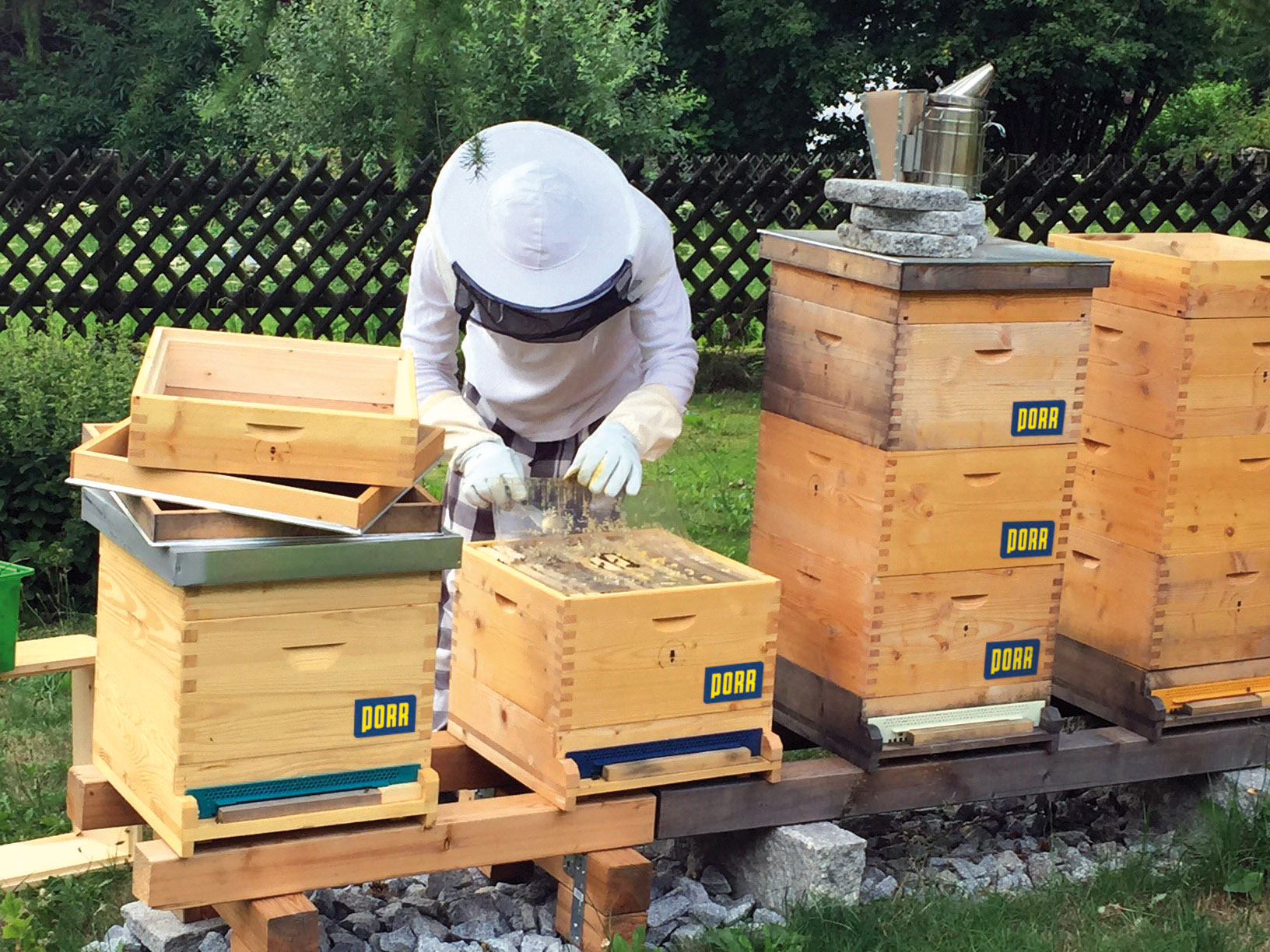 Photo: PORR employee Siegmar Lengauer standing behind his beehives in beekeeper outfit wins honey from honeycomb in his garden.