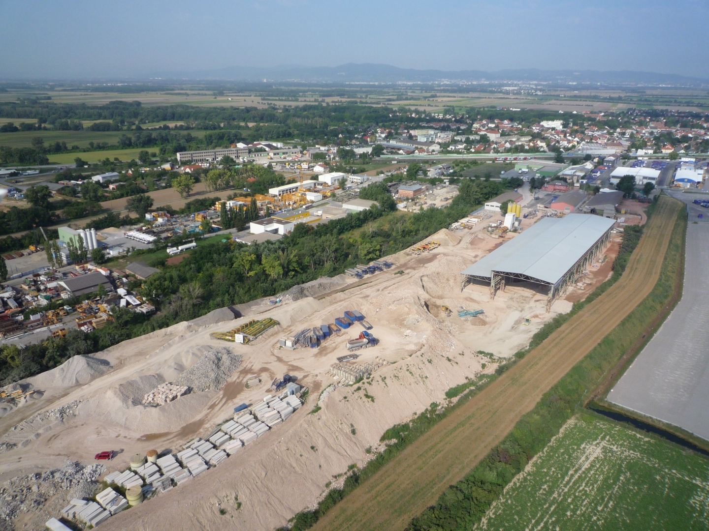 Photo: Recycling plant Himberg: Aerial shot of the vast construction facilities with halls and storage areas for residual construction waste sorted by grades.