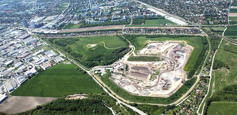 Photo: Aerial view of a landfill site surrounded by grasslands and the beginnings of an urban area.