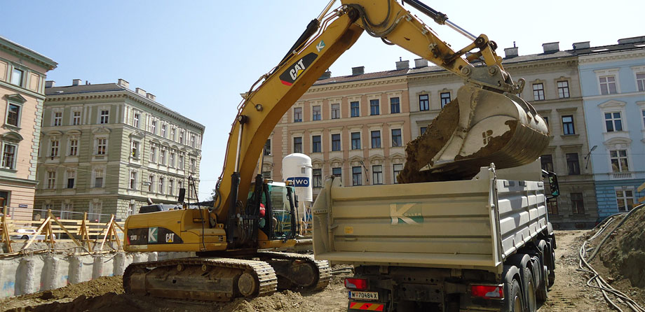 Photo: A crawler excavator loading a lorry with soil on a construction site in the midst of historical buildings.