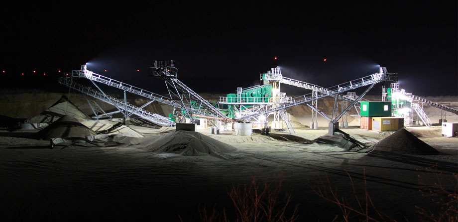 Photo: Nocturnal view of conveyor belts and heaps of gravel, illuminated by spotlights