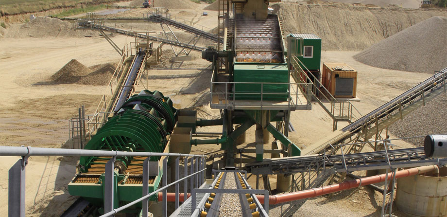 Photo: Conveyor belt system running in different directions in the midst of a large gravel storage site