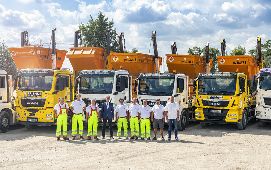 Photo: Group of nine men in front of a row of lorry cranes with skips hoisted above the beds