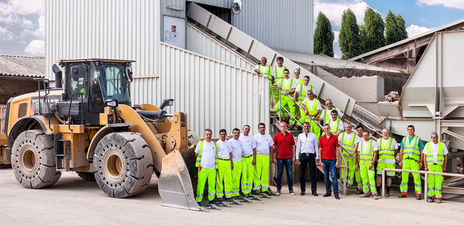 Photo: Group of around 20 men, some of them in work clothes, posing in front of an industrial plant and a wheel loader